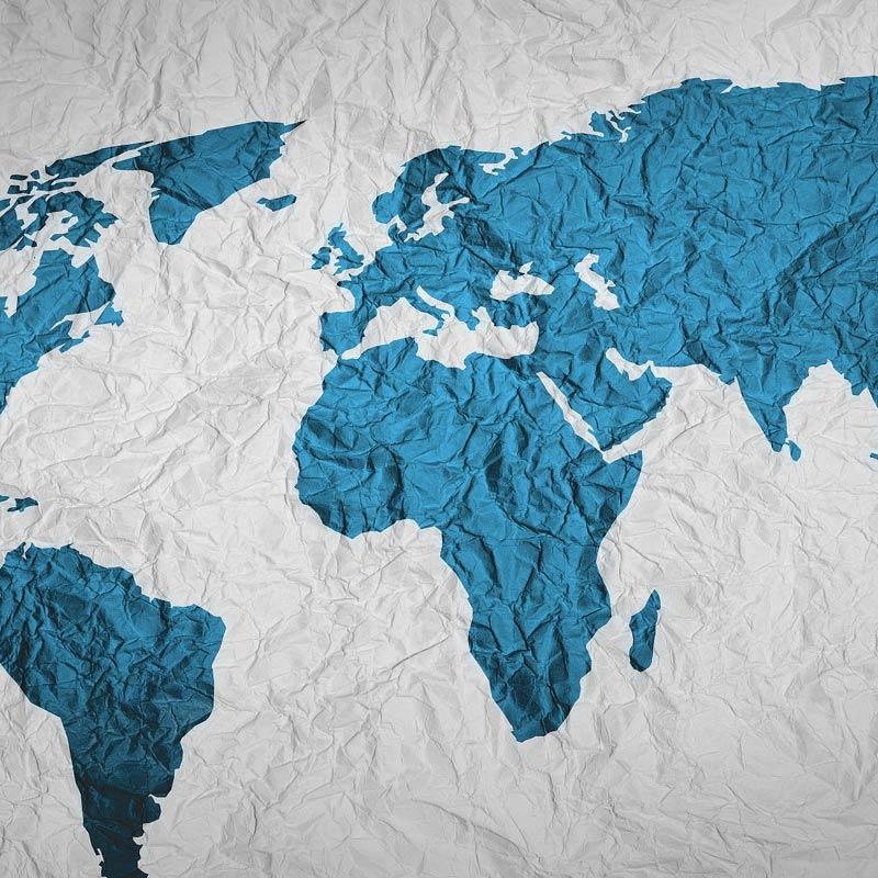grafisch stilisierte Weltkarte mit blau dargestellten Kontinente auf weißem zerknittertem Hintergrund